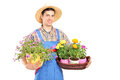 Male gardener with a straw hat holding flower plants isolated on white background Stock Photography