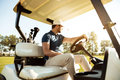 Male golfer driving a cart with golf clubs bag Royalty Free Stock Photo