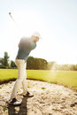 Male golfer hitting ball out of a sand trap Royalty Free Stock Photo