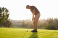 Male Golfer Lining Up Putt On Green Royalty Free Stock Photo