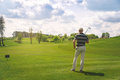 Male golfer standing at fairway on golf course Royalty Free Stock Photo
