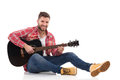 Male guitarist with acoustic guitar in red lumberjack shirt sitting on a floor and play the black full length studio shot isolated Stock Images