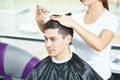 Male hairdresser at work female cutting hair of smiling men client beauty parlour Royalty Free Stock Images