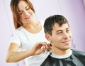 Male hairdresser at work female cutting hair of smiling men client beauty parlour Stock Image