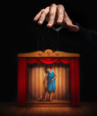 Male hand controlling a small woman puppet Royalty Free Stock Photo