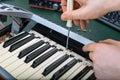 Male hand fixing midi keyboard. Royalty Free Stock Photo