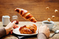 Male hand with flying croissant and coffee Royalty Free Stock Photo