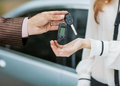 Male hand giving car key to female hand she is holding a cell phone in the background a fragment of the Royalty Free Stock Photography