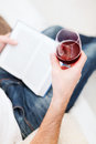 Male hand holdind book and glass of red wine Royalty Free Stock Photo