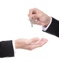 Male hand holding apartment keys and handing it over to another person isolated Royalty Free Stock Photo