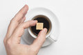 Male hand holding cane sugar cube over cup of black coffee against white background top view with space for text Royalty Free Stock Photo
