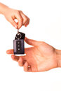 Male hand holding a car key and handing it over Stock Photo