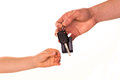 Male hand holding a car key and handing it over to another person Stock Image