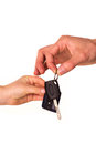 Male hand holding a car key and handing it over to another person Stock Images