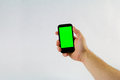 Male hand holding cell phone on white background with green scre Royalty Free Stock Photo