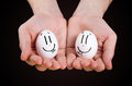 Male hand holding funny eggs with smiley faces Stock Images