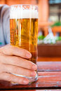 Male hand holding glass of freshly tapped beer close up Royalty Free Stock Image