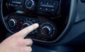 Male hand pressing button in modern car