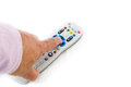Male hand pressing silver remote control on white with copy-spac Royalty Free Stock Photo