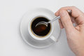 Male hand stir slowly black coffee with spoon in coffee cup against white background with place for text top view Royalty Free Stock Photo