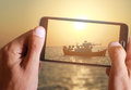 Male hand taking photo of a boat in the sea in sunset with cell, mobile phone. Royalty Free Stock Photo