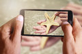 Male hand taking photo of sea star in little boy, child hand with cell, mobile phone. Royalty Free Stock Photo