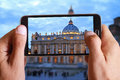 Male hand taking photo of st peter basilica in Vatican with cell, mobile phone. Europe travel, Italian holiday. Royalty Free Stock Photo