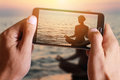 Male hand taking photo of Yoga woman meditatiing in lotus pose on the beach during sunset with cell, mobile phone. Royalty Free Stock Photo