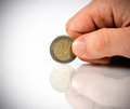 Male hand with two euro coin reflection Stock Photo