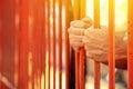 Male hands behind prison yard bars