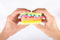 Male hands holding a burger made from sponges different colors. Concept of unhealthy food and non-natural products