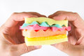 stock image of  Male hands holding a burger made from sponges different colors. Concept of unhealthy food and non-natural products