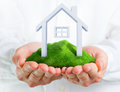 Male hands holding a green hill with a small house Stock Photo