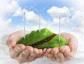 Male hands holding a green hill with wind turbines Stock Images
