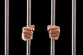 Male hands holding prison bars isolated on black background Royalty Free Stock Photo
