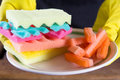 Male hands in yelliw gloves holding a burger made from sponges different colors. Concept of unhealthy food and non