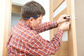 Male handyman carpenter at interior wood door lock installation Royalty Free Stock Photo