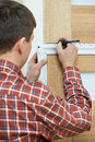 Male handyman carpenter at interior wood door lock installation with angle Stock Photos