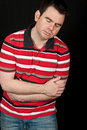 Male having chest pain on black backdrop Royalty Free Stock Image