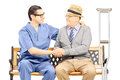 Male healthcare professional comforting an elderly gentleman sea seated on bench isolated on white background Stock Image