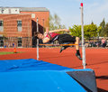 Male High school athlete tries to clear bar in high jump in track meet Royalty Free Stock Photo