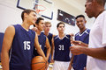 Male high school basketball team having team talk with coach in gymnasium smiling Stock Images