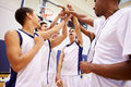 Male high school basketball team having team talk with coach whilst raising their arms in the air Royalty Free Stock Photography