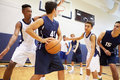 Male high school basketball team playing game in gymnasium Royalty Free Stock Photography