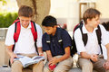 Male high school students hanging out on school campus close up of sitting outside Stock Image