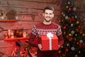 Male holding a big red ribbon gift box and smiling. Royalty Free Stock Photo