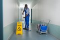 Male janitor mopping in corridor young african cleaning floor Royalty Free Stock Images