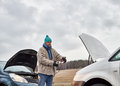 Male and jumper cables mid adult man use a between the two vehicles Stock Image