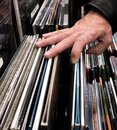 Male in leather jacket browsing through vinyl albums at a record store Royalty Free Stock Photo