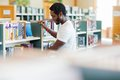 Male librarian arranging books in bookstore side view of african american Royalty Free Stock Images